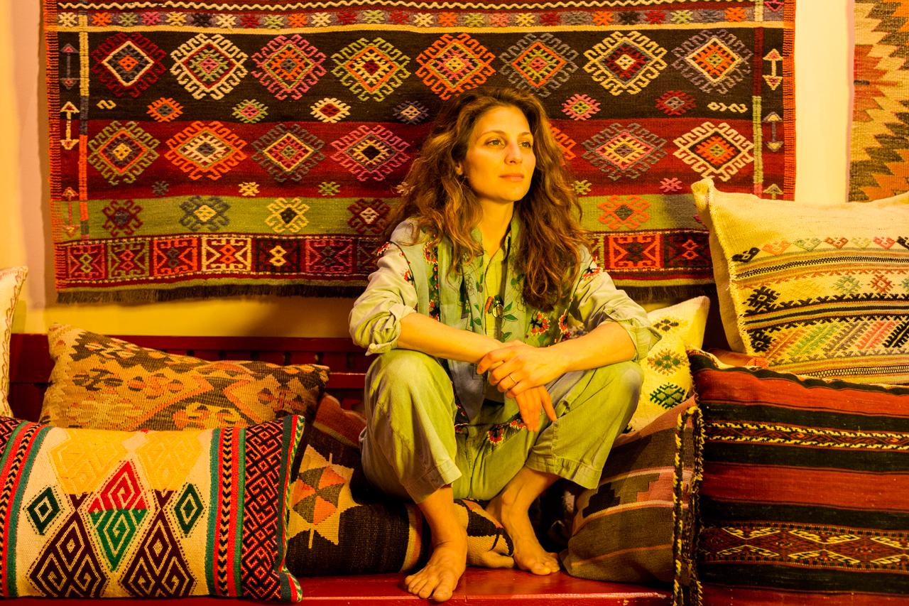 Beyza Nur Özler in ihrem Laden im Kollwitzkiez, umgeben von Kilims