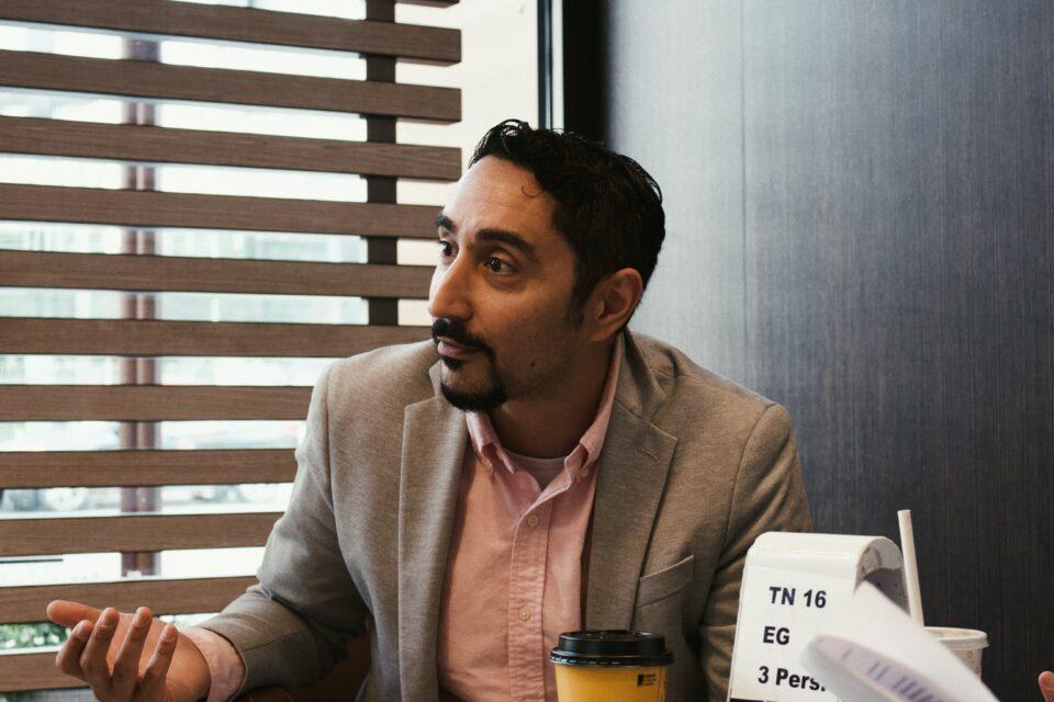 Mann sitzt am Tisch und ist im Gespräch.