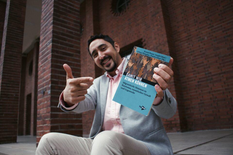 Mann hält lächelnd das Buch in die Kamera.